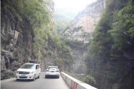 如图所示,驾驶机动车在这样的路段遇前方两车交会应及时减速。
