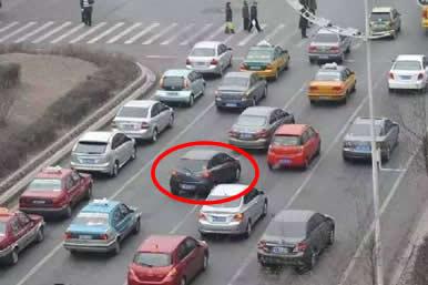 如图所示,红圈标注的深色车辆的做法是违法的。